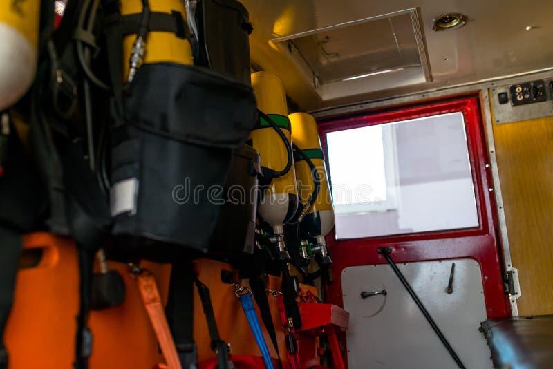 Gelbe Sauerstoff-Flaschen für Feuerwehrmänner, gelegt in ein altes Löschfahrzeug stockfoto