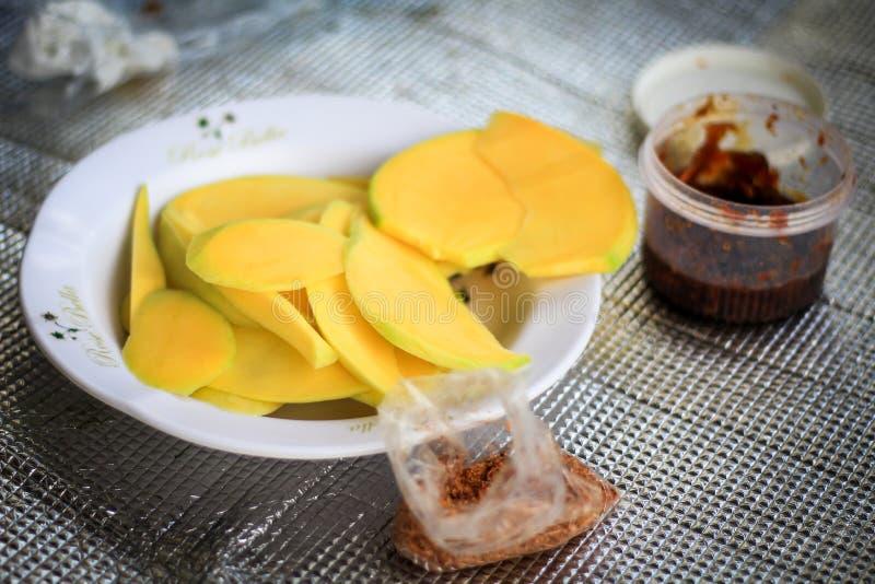 Gelbe Scheibe der Mango und der süßen Soße lizenzfreie stockbilder