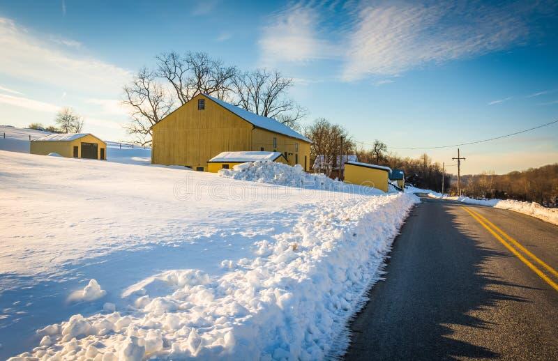 Gelbe Scheune und ein Schnee setzten Forderung entlang einer Landstraße in Yor durch lizenzfreie stockbilder