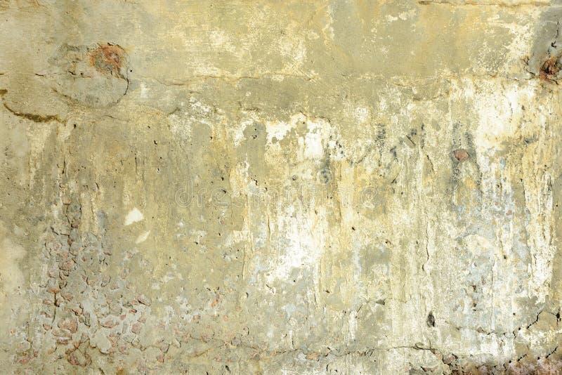 Gelbe schmutzige Betonmauer mit Sprüngen und Löchern Hintergrund mit Beschaffenheit lizenzfreies stockfoto