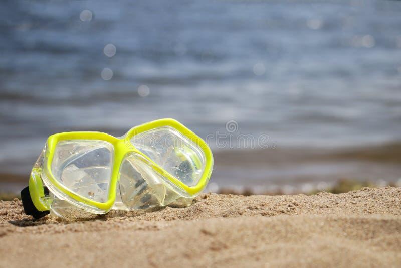 Gelbe schnorchelnde schwimmende Maske auf der sandigen Küste stockbild