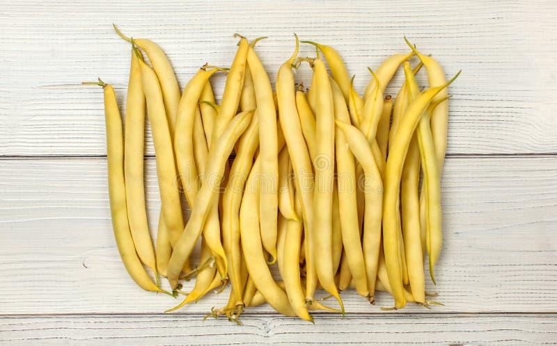 Gelbe Schnurwachsbohnen auf weißen Brettern Tischplattenansicht lizenzfreie stockbilder