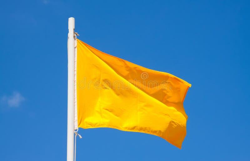 Gelbe Signalflagge am Himmelhintergrund lizenzfreie stockbilder