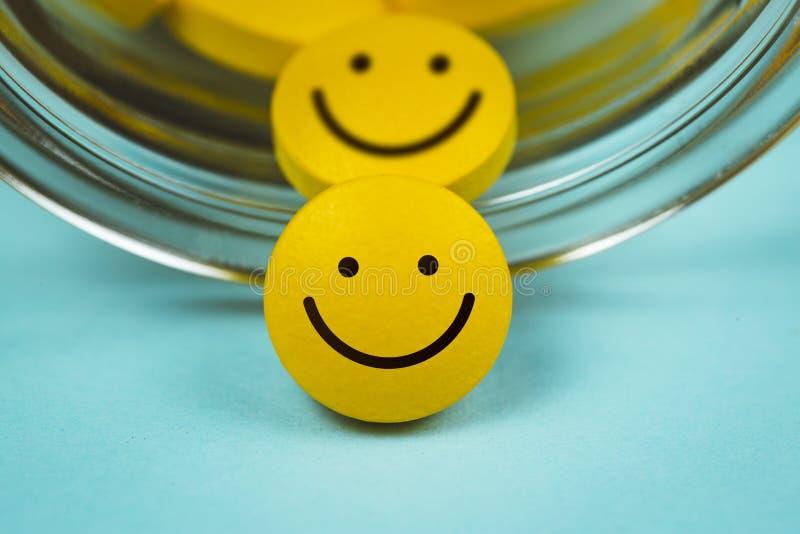 gelbe smileypillen, die aus einem gestürzten Tablettenfläschchen heraus verschüttet werden lizenzfreies stockbild