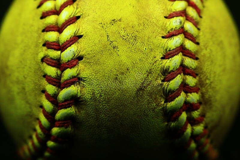 Gelbe Softballnahaufnahme mit Rotnähten auf schwarzem Hintergrund stockfotografie