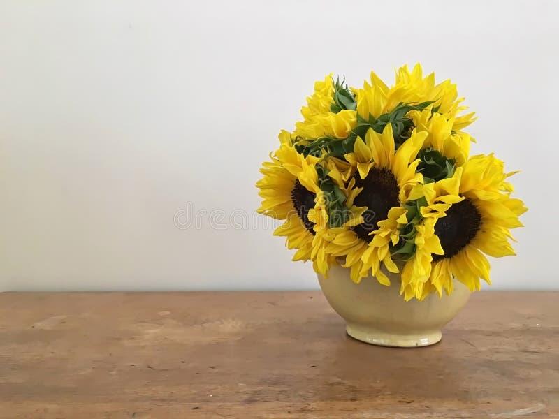 Gelbe Sonnenblumen in der Blüte in einem Weinlese-Vase mit einem neutralen Hintergrund auf einer warmen Holzoberfläche lizenzfreie stockfotos