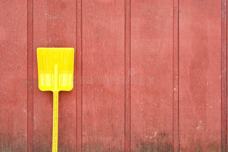Gelbe Spielzeugschaufel gegen rote Stallwand lizenzfreie stockfotos