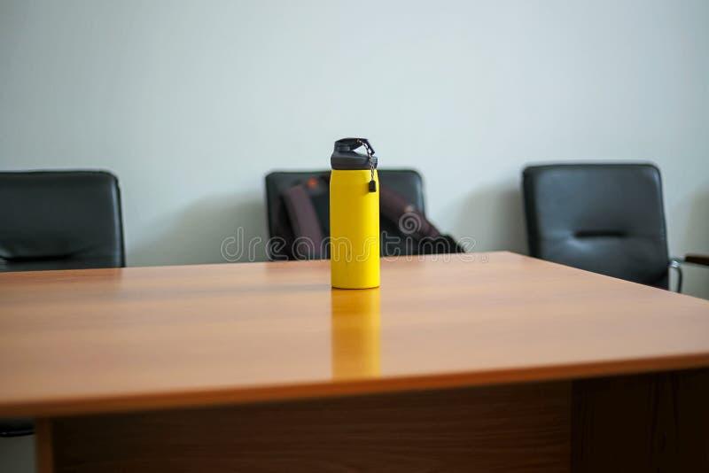 Gelbe Sportflasche mit Wasser auf einem Holztisch Selektiver Fokus lizenzfreie stockfotos