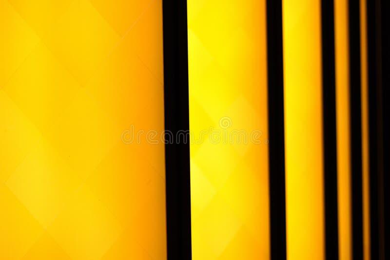Gelbe Streifen beleuchtet auf schwarzer Hintergrund Musterzusammenfassung stockbilder