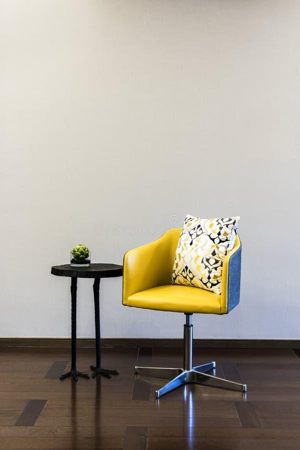 Gelbe Stuhlkombination des Holztischs vor einer einfachen Wand lizenzfreie stockbilder