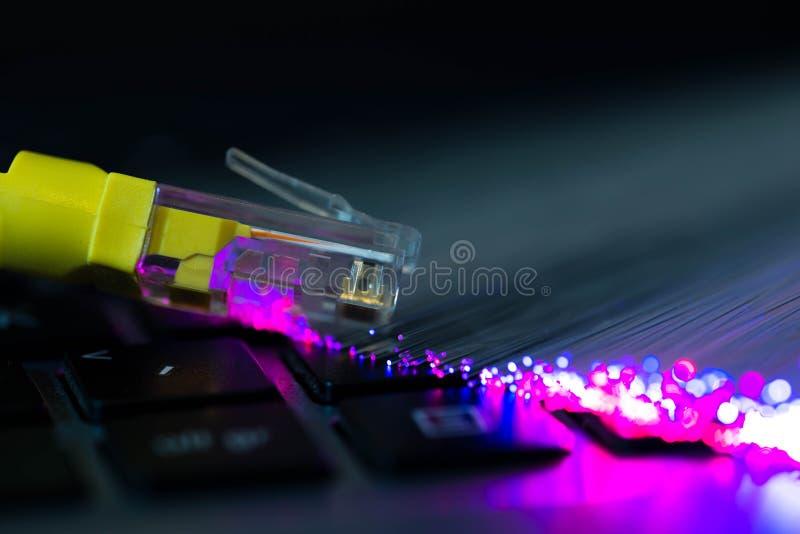 Gelbe Tastatur Laptop-Computer des Internet-Anschaltung, glühende bunte Glasfasern stockfoto