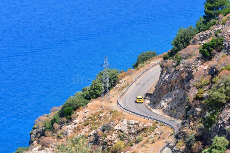 Gelbe Taxiauto-Antriebe entlang der Mittelmeerstraße zwischen Bergen nahe der Küstenlinie stockbilder