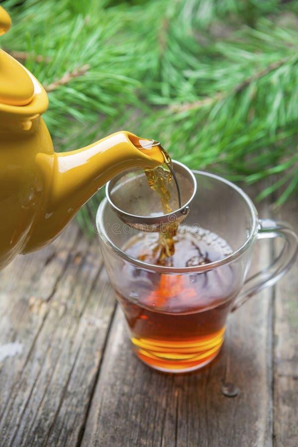 Gelbe Teekanne, die schwarzen Tee in der Glasschale auf Holztisch gießt lizenzfreies stockfoto