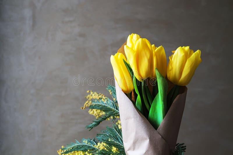 Gelbe Tulpen auf einem grauen Hintergrund stockbilder