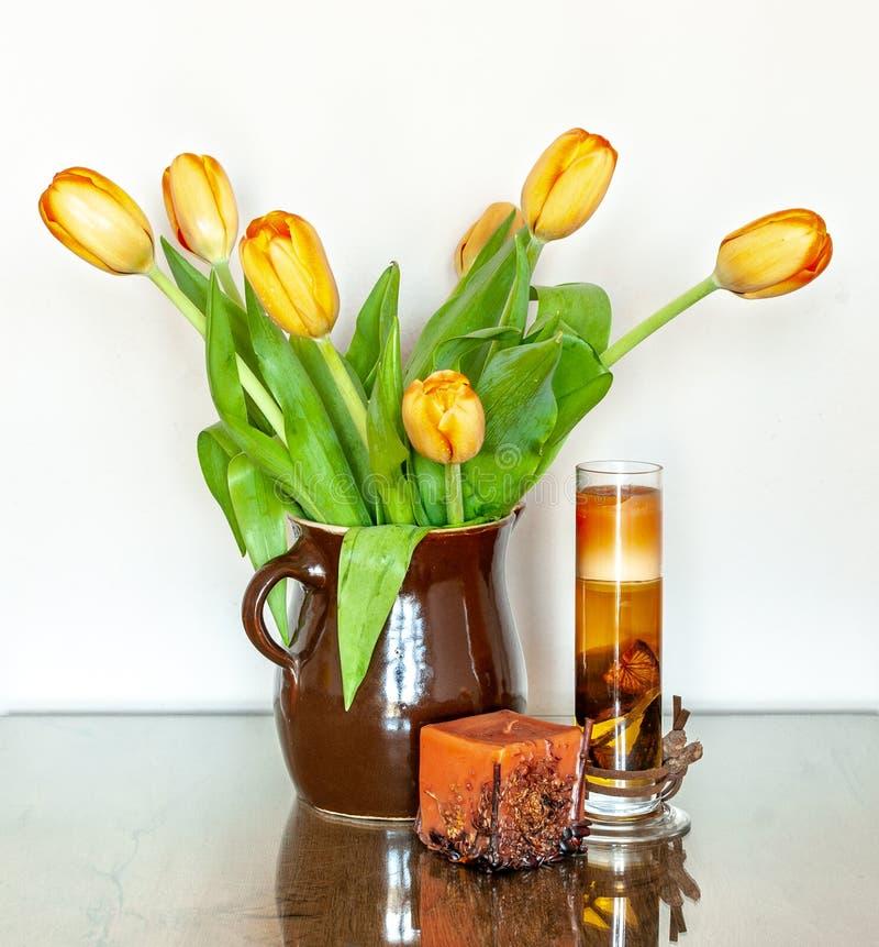 Gelbe Tulpen in Clay Jug auf einem Glastisch lizenzfreie stockbilder
