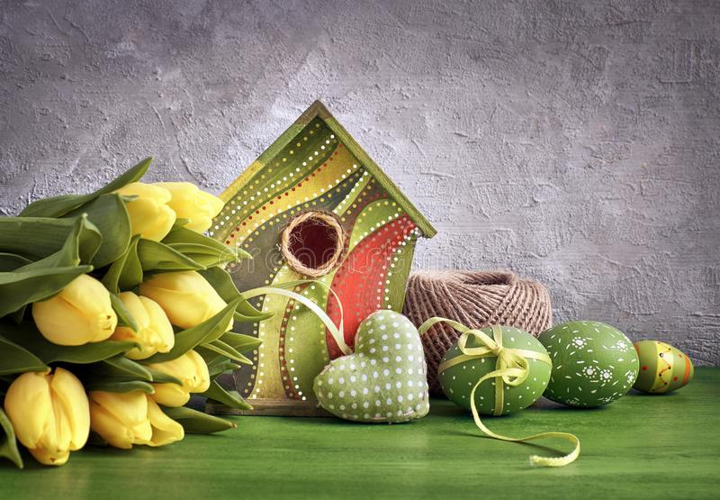 Gelbe Tulpen, Vogelhaus und gemalte Ostereier mit angefüllt ihm lizenzfreie stockbilder