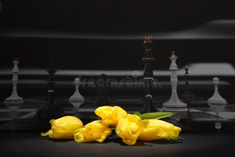 Gelbe Tulpen vor dem hintergrund eines schwarzen Schachbretts lizenzfreie stockfotos