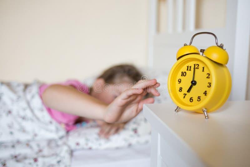 Gelbe Uhr ist zeigt auf dem Tisch sieben O-` Uhr Schulkind wacht auf und stellt die Warnung ab stockfotografie