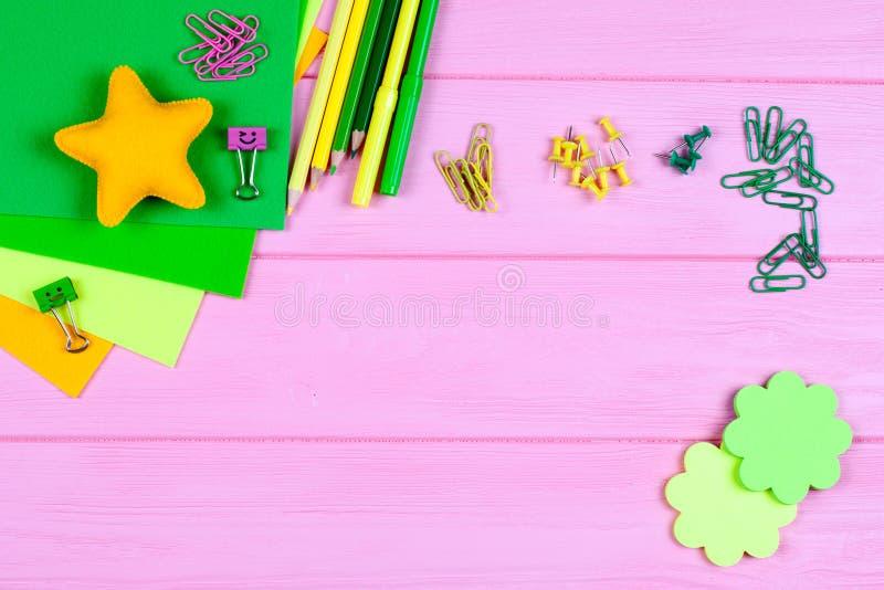 Gelbe und grüne Bleistifte, Filzstifte, Briefpapier, Büroklammern, Briefpapiernägel, Filz und Lächeln auf rosa hölzernem Hintergr stockbild