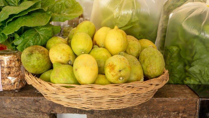 Gelbe und gr?ne Hautzitrone in einem braunen Korb, frisches organisches Kopfsalatgem?se in der Plastiktasche auf Holztisch in ein lizenzfreies stockbild