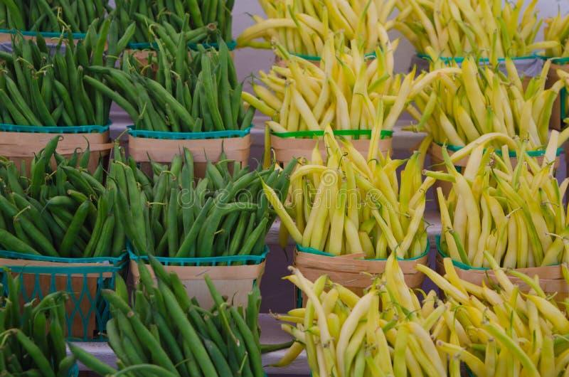 Gelbe und grüne Stangenbohnen in den hölzernen Körben der Landwirte am Markt stockfotografie
