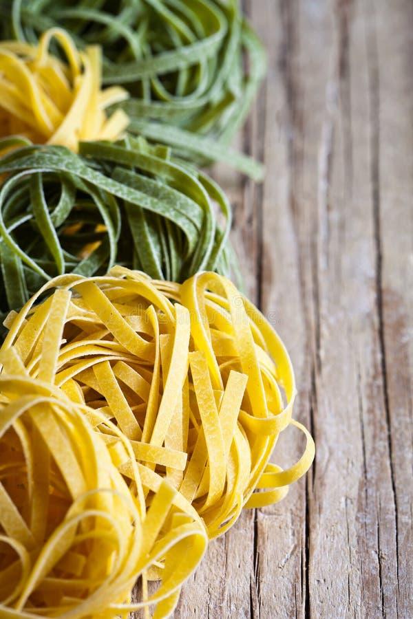 Gelbe und grüne ungekochte Teigwarenbandnudeln stockbilder