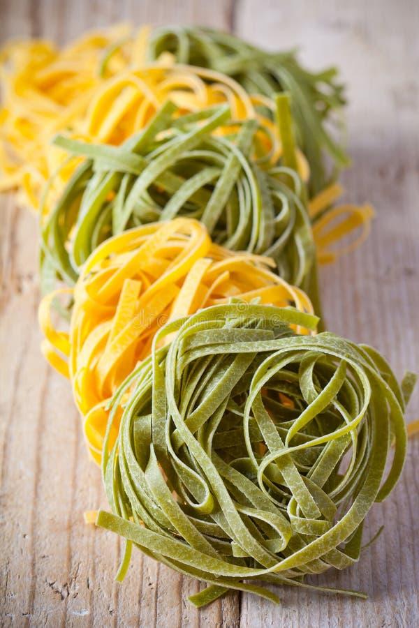 Gelbe und grüne ungekochte Teigwarenbandnudeln stockfotos