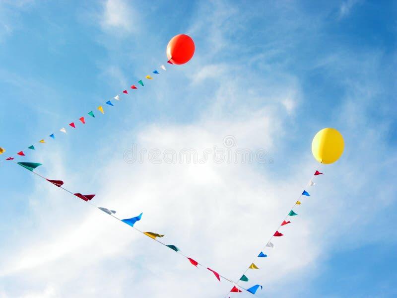 Gelbe und rote Ballone, die in blauen Himmel fliegen stockbild