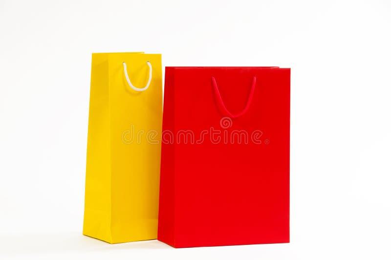 Gelbe und rote Papiertüte auf einem weißen Hintergrund lizenzfreie stockfotografie