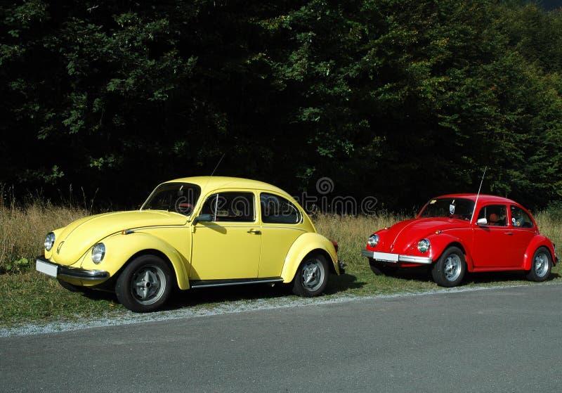 Gelbe und rote VW-Käfer stockfotos