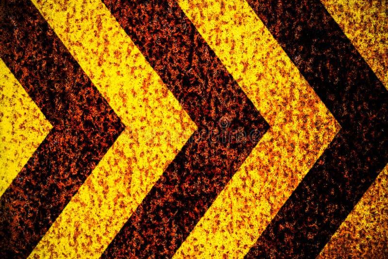 Gelbe und schwarze Streifen des warnenden Warnschildes als Pfeile gemalt über rostiger Metallplatte als Beschaffenheitshintergrun stock abbildung