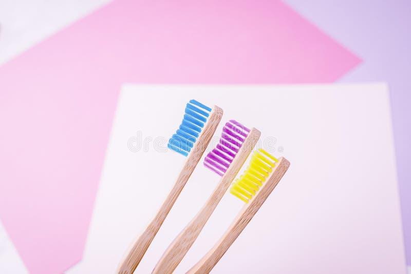 Gelbe, violette und blaue Bambuszahnbürsten Umweltfreundliches Konzept Minimaler, farbiger geometrischer Hintergrund Kopieren Sie lizenzfreie stockfotos