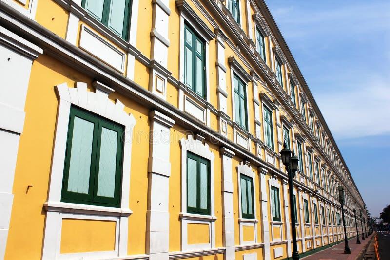 Gelbe Wand mit vielen grünen Fenstern stockfotos