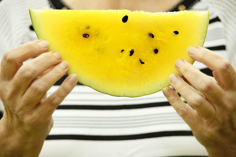 Gelbe Wassermelone in der Hand stockbilder