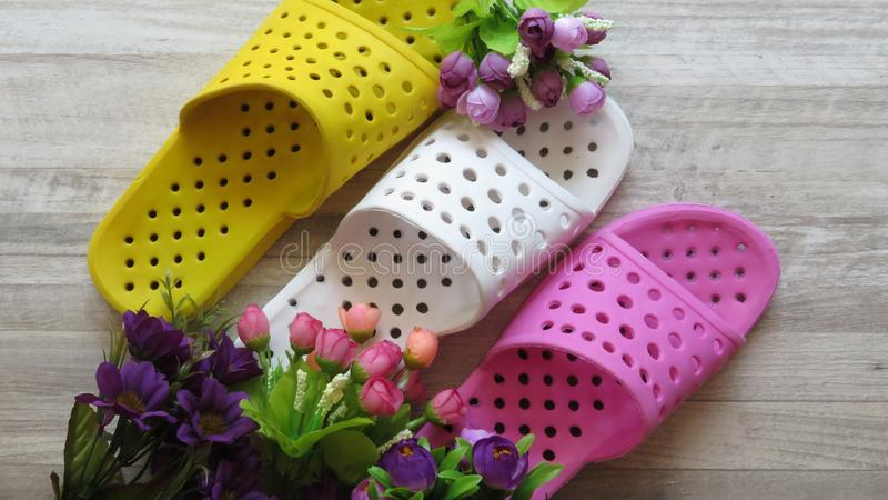 Gelbe, weiße und rosa Duschsandalen/Bad-Pantoffel und Blumen schnell trocknend stockbilder