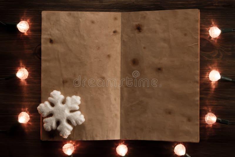 Gelbe Weihnachtslichter mit einem leeren Buch auf hölzernem Hintergrund stockbild