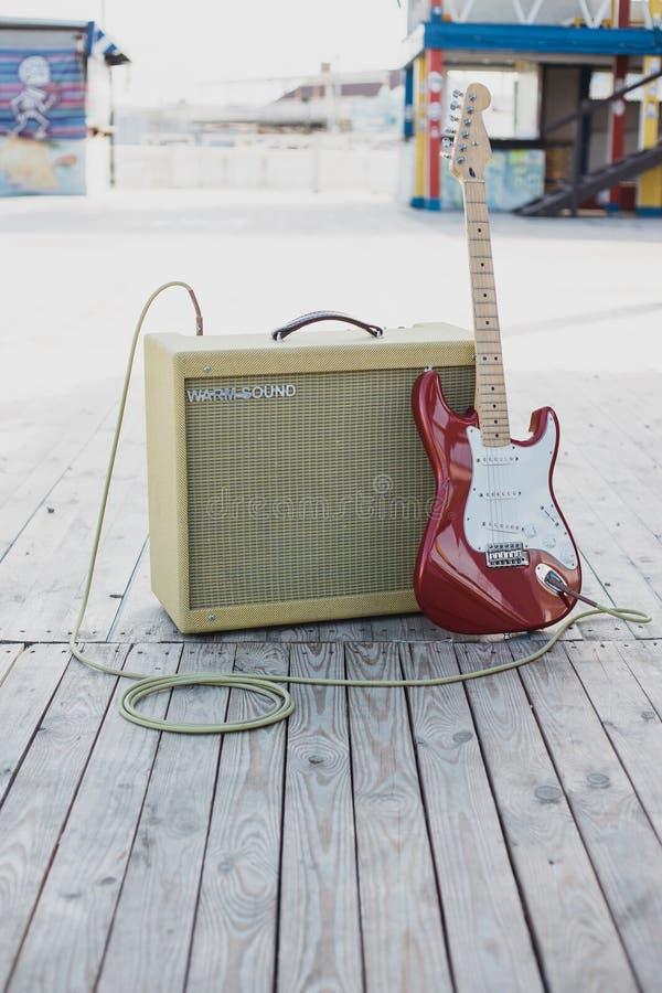 Gelbe Weinlesegitarre aplifier mit Kabel und roter E-Gitarre lizenzfreie stockfotografie