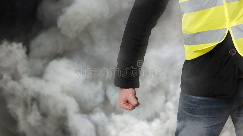 Gelbe Westenproteste Unerkennbarer Mann preßte seine Faust im Protest im Tränengas zusammen Das Konzept der Revolution und des Pr stockbild