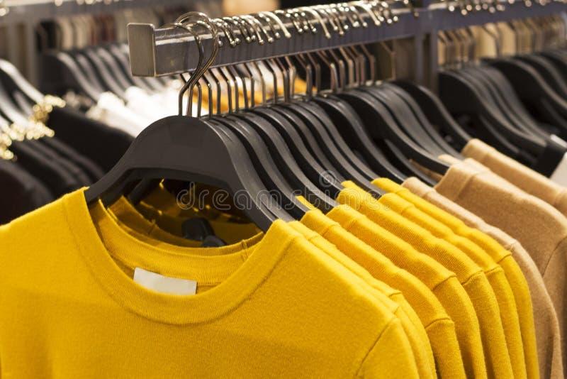 Gelbe woolen gestrickte Strickjacken Tendenz-Ceylons, die an den Aufhängern im Speicher, Nahaufnahme hängen stockfotografie