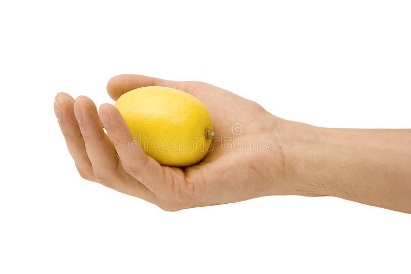 Gelbe Zitrone in einer Hand lizenzfreie stockfotografie