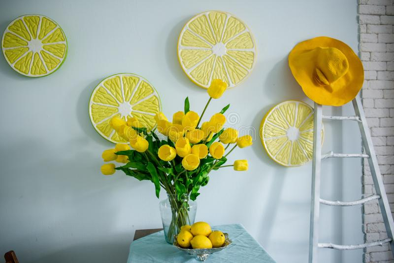 Gelbe Zitronen und gelbe Tulpen auf dem Tisch stockfotos
