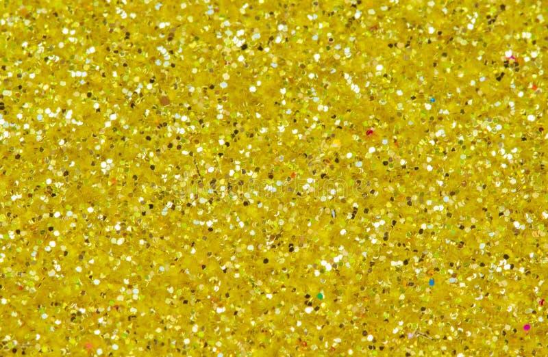 Gelber abstrakter Hintergrund Goldfunkeln-Nahaufnahmefoto Goldenes Schimmerpackpapier stockfotografie
