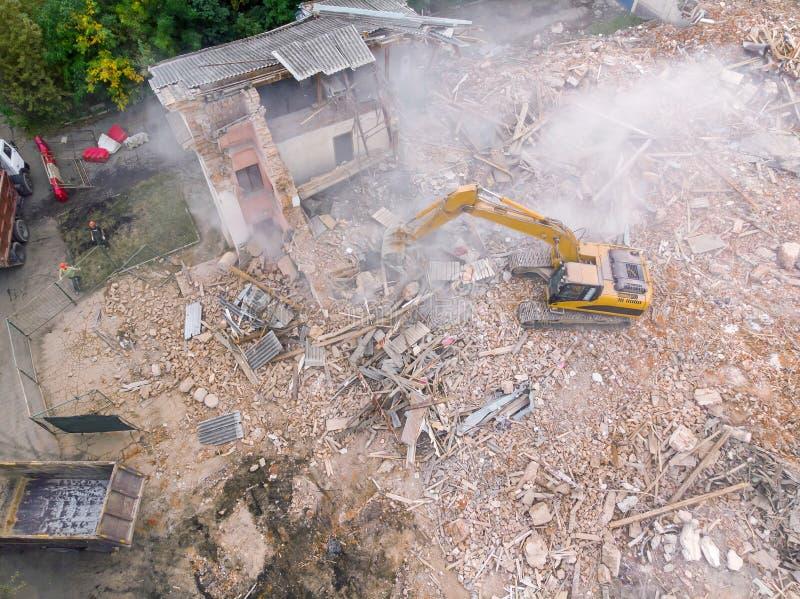 Gelber Bagger, der das Gebäude am Abbruchgelände zerquetscht stockfoto