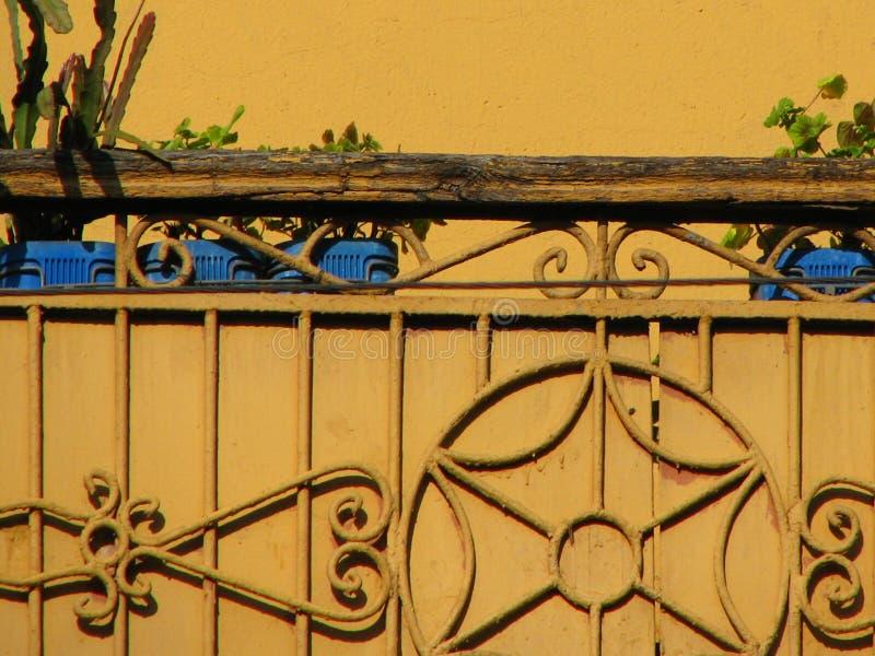Gelber Balkon der Weinlese mit Metalldekoration und alter hölzerner Schiene stockfotografie