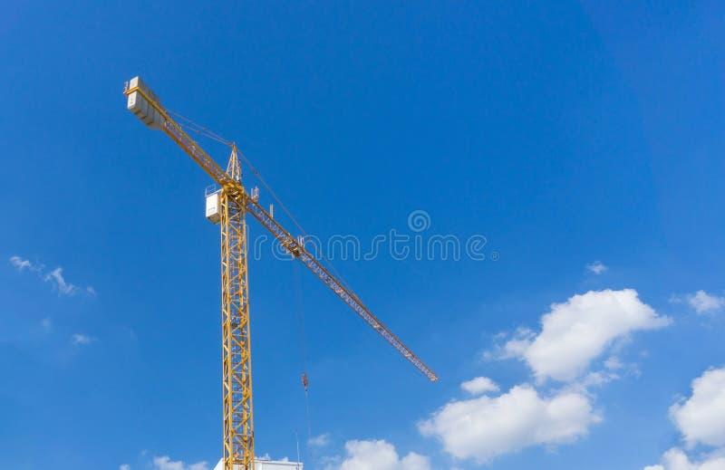 Gelber BauTurmkran gegen blauen Himmel stockfotos