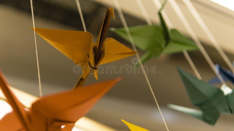 Gelber, blauer, roter Origamivogel auf grauem Hintergrund lizenzfreie stockbilder