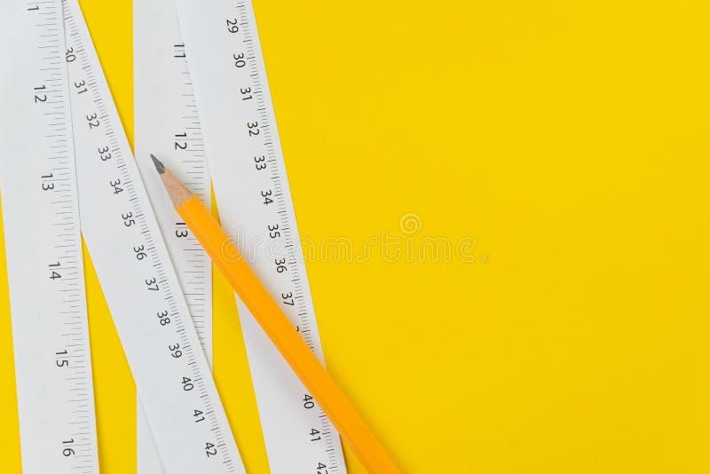 Gelber Bleistift und weiße messende Bänder mit Zentimeter und Zoll auf klarem gelbem langen oder des Herstellers Instrument des H lizenzfreie stockbilder