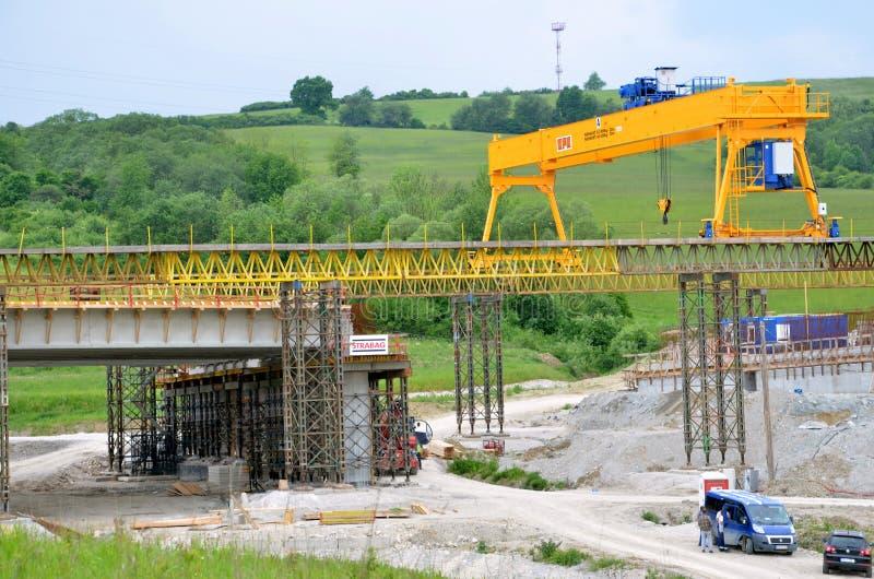 Gelber Brückenkran auf Baustelle der Landstraße des Slovak D1 Außer dem Kran gibt es einige Arbeitskräfte und Autos lizenzfreie stockfotografie