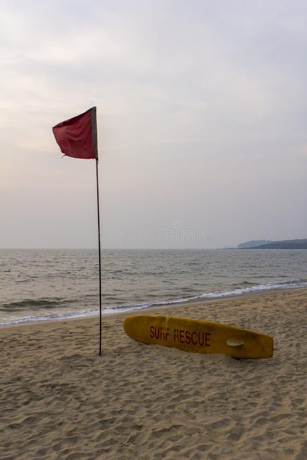 Gelber Brandungsbrettleibwächter um die Schwimmen der roten Fahne wird auf einem leeren sandigen Strand gegen das Meer im schlech stockfotografie