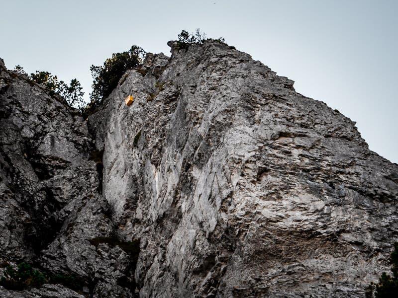 Gelber Briefkasten weit oben an einem steilen Berg schwer zugänglich Briefkasten lustig stockbild